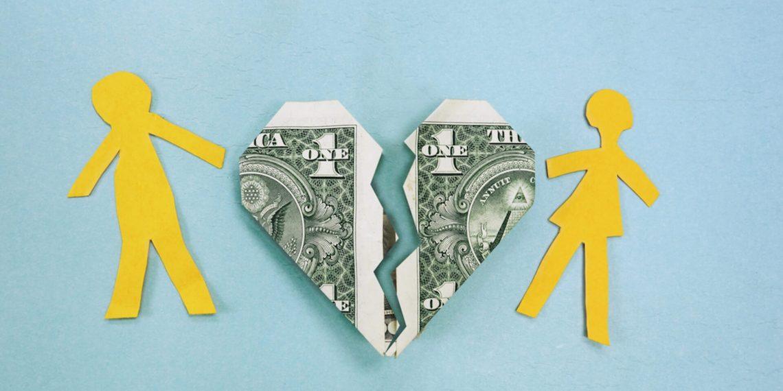 Heart-shaped dollar bill breaking in between two people
