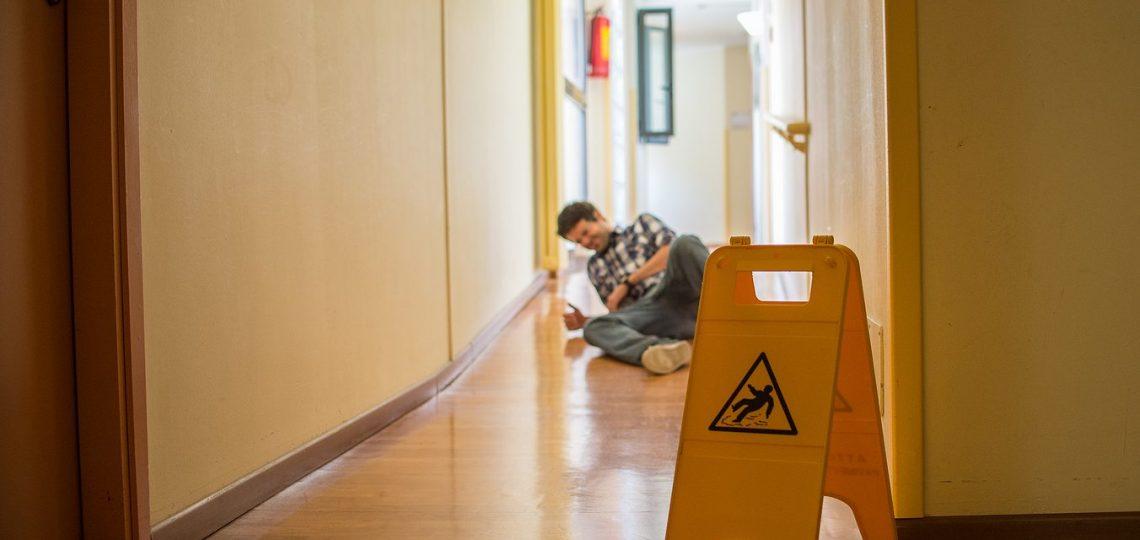 Man slips on wet floor. Wet floor danger sign in the foreground. Concept of danger slipping