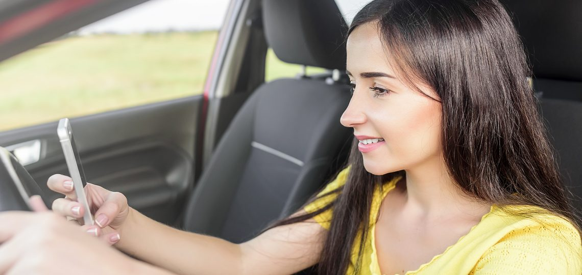 Smiling woman using phone at the wheel of her car.